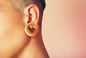 A piece of jewelry that fits into a stretched earlobe hole. Man with ear tunnel. Male ear with a ring