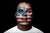 Man with EEUU flag painted on her face on black background