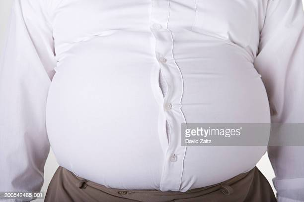 Man with enlarged stomach, too small shirt, mid section, close-up