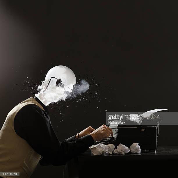 Man with exploding lightbulb head on retro typewriter