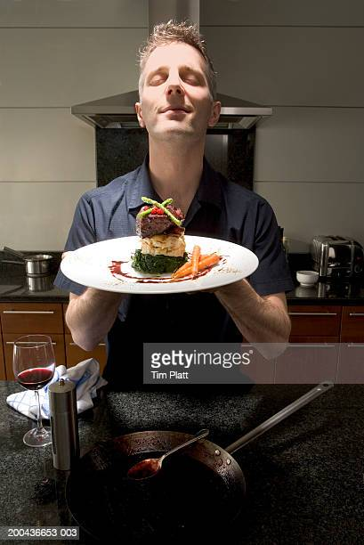 Man with eyes closed holding plate of gourmet meal, close-up