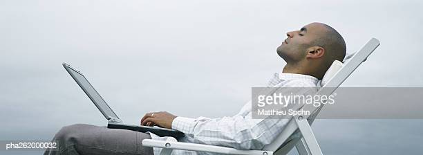 Man with eyes closed in lounge chair with laptop on lap, sky in background, side view