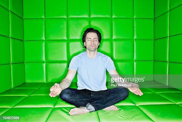Homme avec les yeux fermés méditation en posture de lotus en Pièce capitonnée
