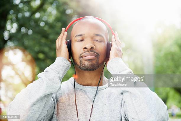 man with eyes closed wearing headphones