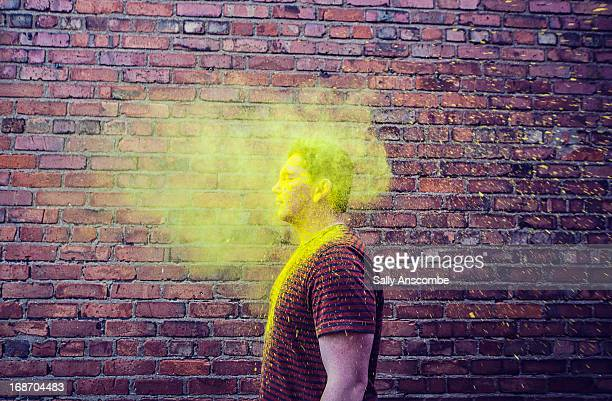 Man with face hidden in a yellow cloud