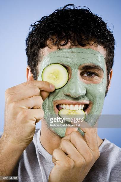 Man with facial mask and cucumber slices