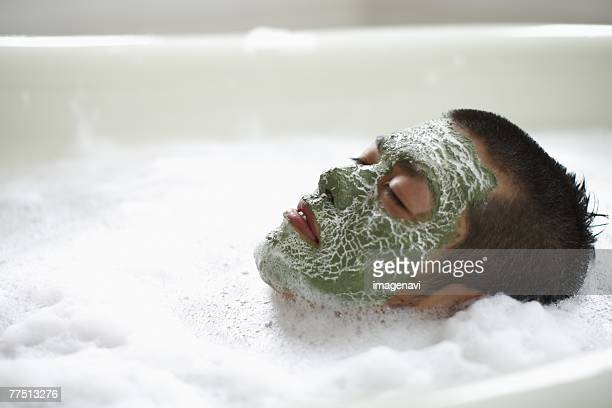 Man with Facial Mask Lying in Foam Bath