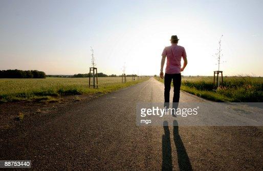 Man with fedora walking at sunset