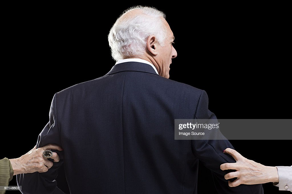 Man with female hands grabbing his arms : Stock Photo