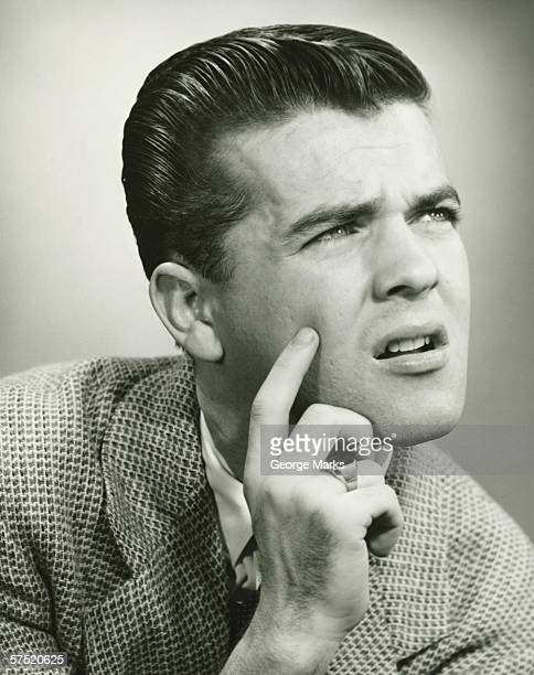 Man with finger on face, thinking, posing in studio, (B&W), portrait