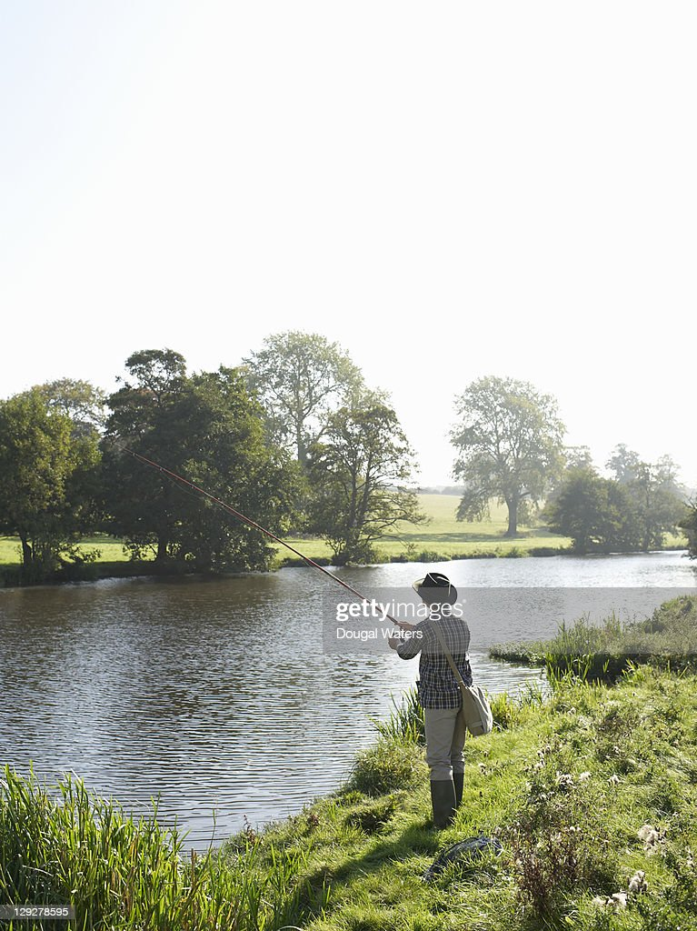 Man with fishing rod by lake. : Stock Photo