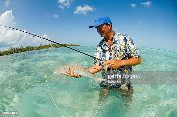 Man with fishing rod, standing in emerald green water, holding bonefish