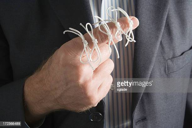 Man with five pieces of string tied in a bow on his finger