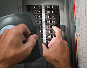 man throwing circuit breaker at residential service panel