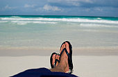 Man with flip flops relaxing on the beach