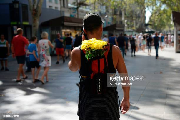 A man with flowers in fis backpack walks on the Rambla boulevard on August 18 2017 a day after a van ploughed into the crowd killing 13 persons and...