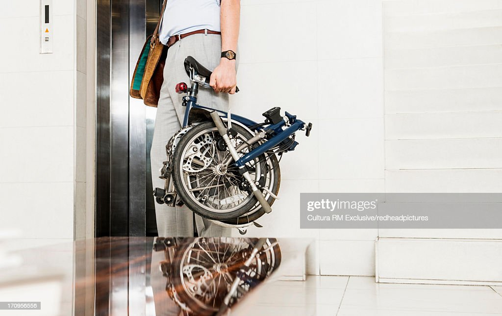 Man with folding bicycle by elevator
