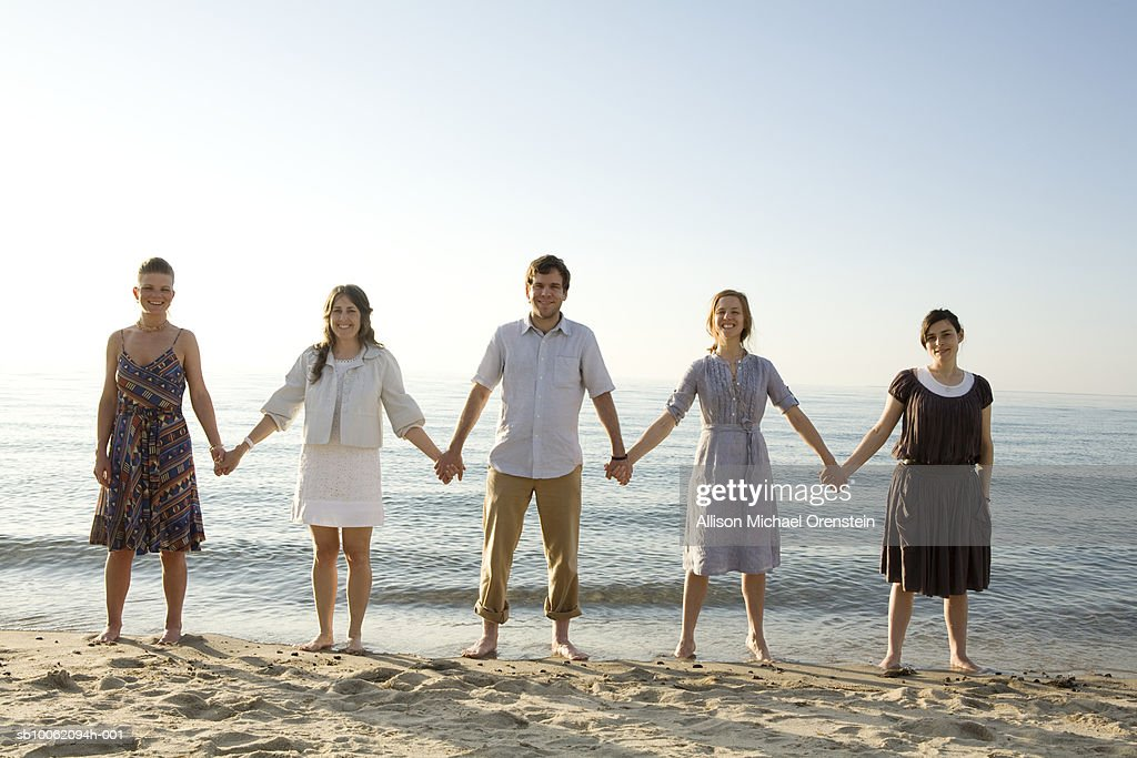 Man with four women holding hands on beach, portrait : Stock Photo