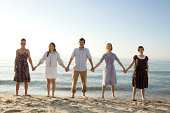 Man with four women holding hands on beach, portrait