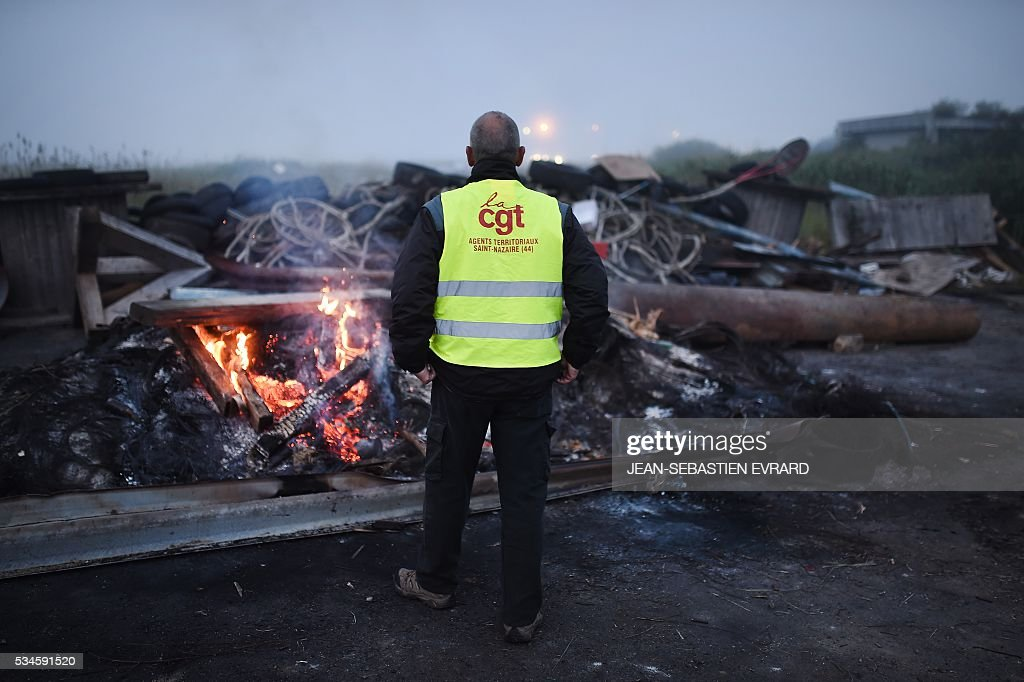 A man with French CGT union's jacket looks at fire as workers on strike block the access to an oil depot near the Total refinery of Donges, western france, on May 27, 2016 to protest against the government's planned labour law reforms. The French government's labour market proposals, which are designed to make it easier for companies to hire and fire, have sparked a series of nationwide protests and strikes over the past three months. French unions on May 27 called on workers to 'continue and step up their action', as a wave of strikes against a disputed labour law disrupted transport and fuel supplies. / AFP / JEAN