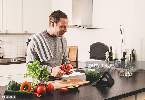 Man with fresh vegetables in kitchen