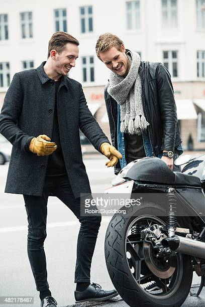 Man with friend pointing at motorcycle