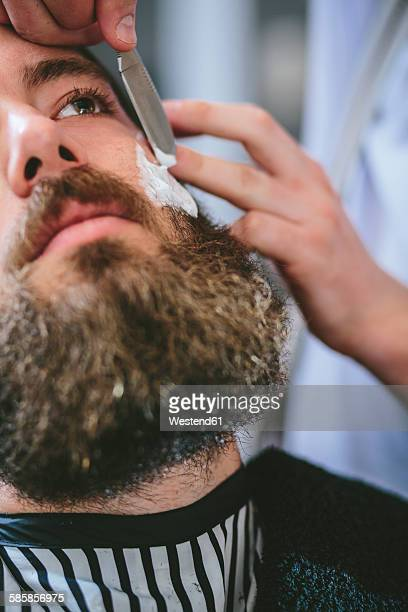 Man with full beard getting a shave at the barber