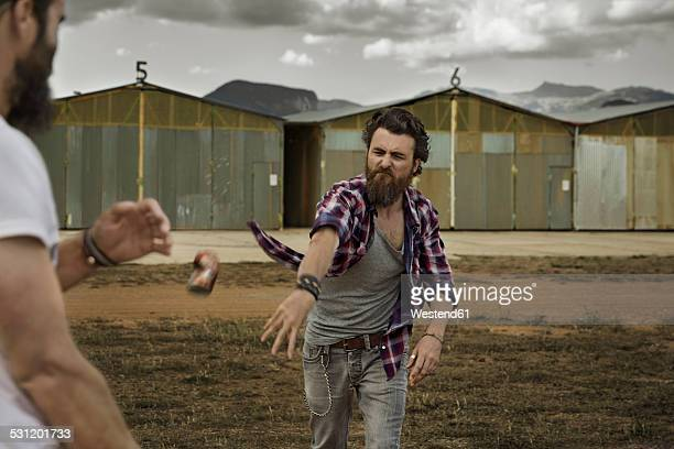 Man with full beard throwing beverage can to opponent