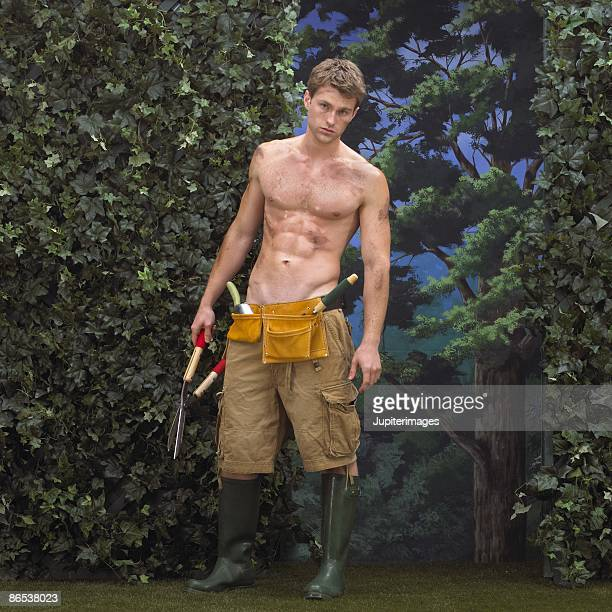 Man with gardening tools near hedge