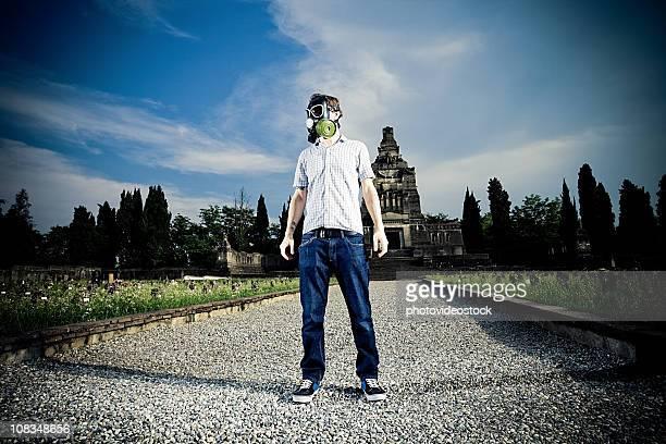 Uomo in maschera antigas in un cimitero