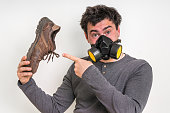 Man with gas mask is holding dirty stinky shoe - unpleasant smell concept