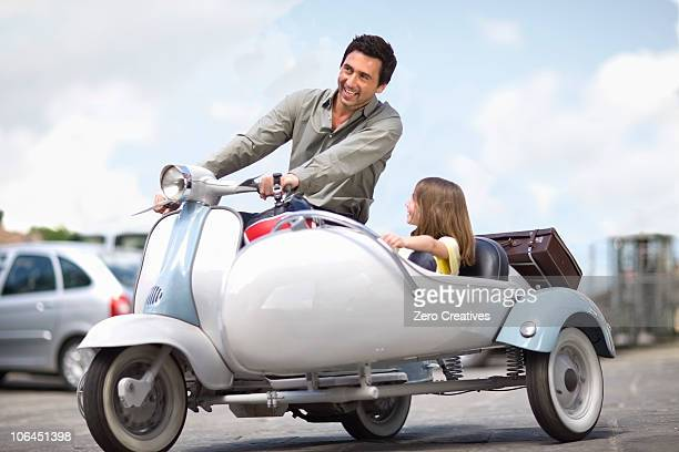 Man with girl driving a vespa