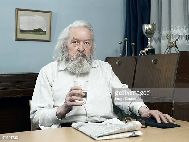 Man with glass of water and newspaper