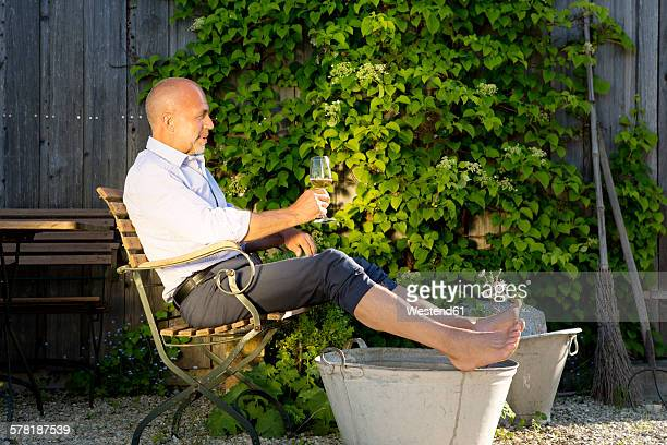 Man with glass of white wine taking footbath in a garden