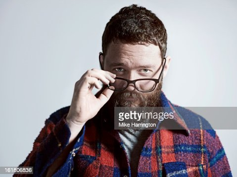 Man with glasses and beard looking to camera.