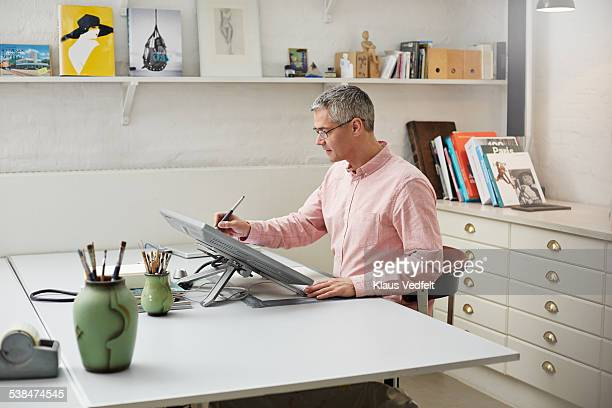 Man with glasses working w. digital pen on screen