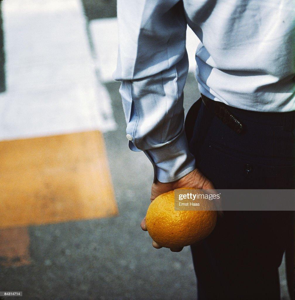 A man holding a grapefruit behind his back, Japan, May 1983.