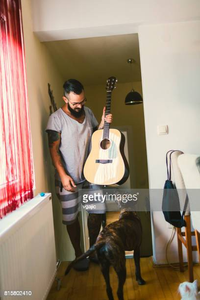 Man with guitar and dog at home
