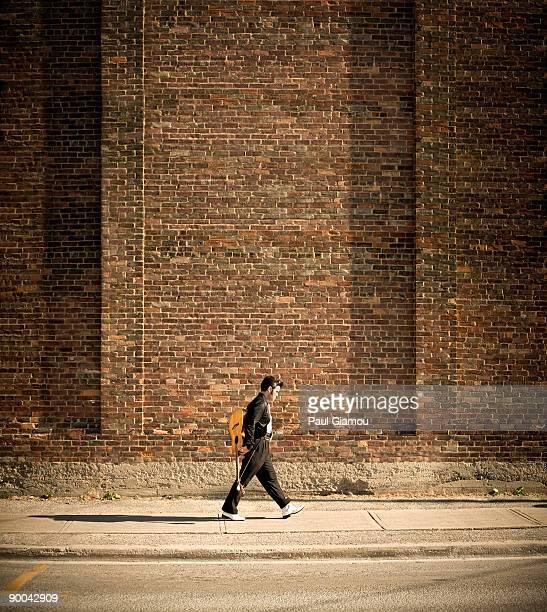 Man with guitar walking on sidewalk