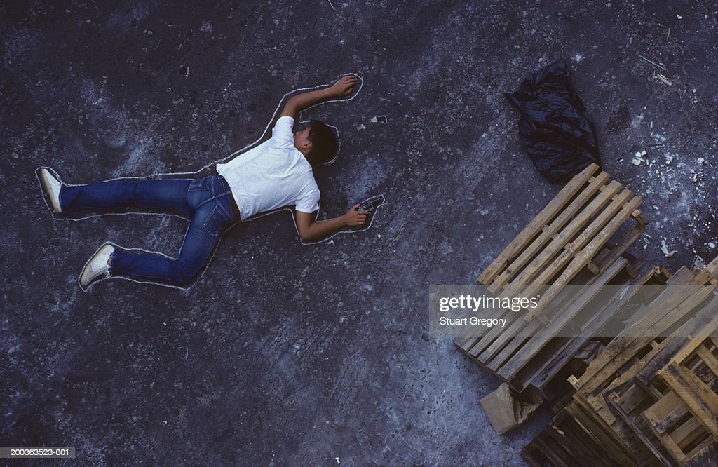 Man with gun lying on ground, chalk outline around him, elevated view : Stock Photo