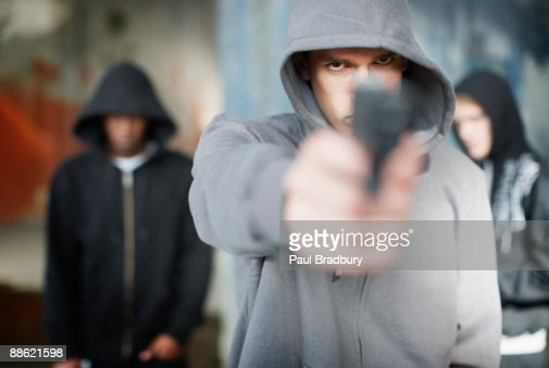 Man with gun pointed at viewer : Stock Photo