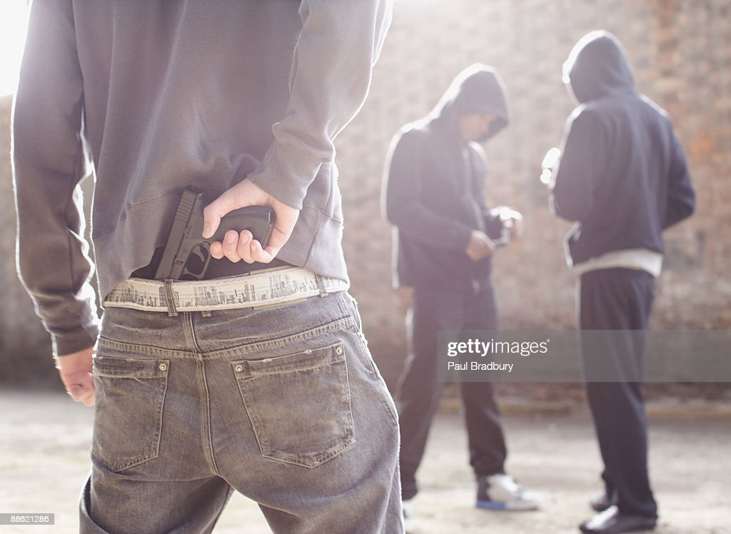 Man with gun robbing drug dealers : Stock Photo