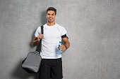 Portrait of young man athlete with bag and bottle of water. Fitness guy isolated over grey background looking at camera. Latin man listening to music after workout and leaning against grey wall.