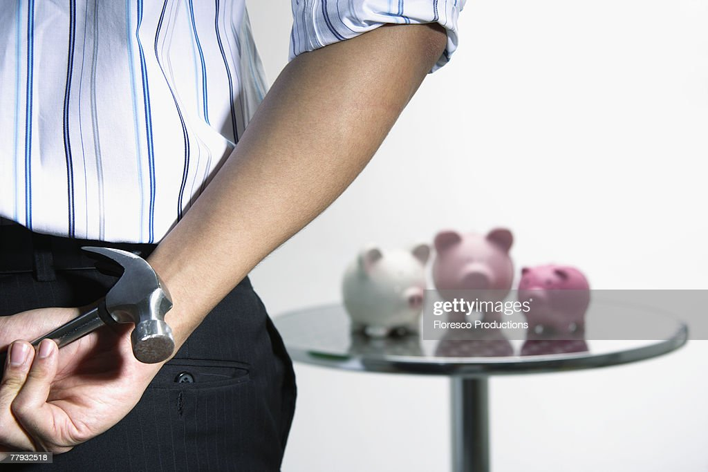 Man with hammer approaching three piggybanks on table : Stock Photo