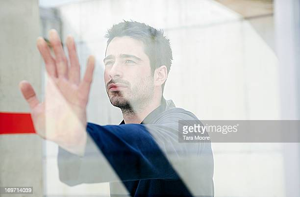 man with hand on glass at train station
