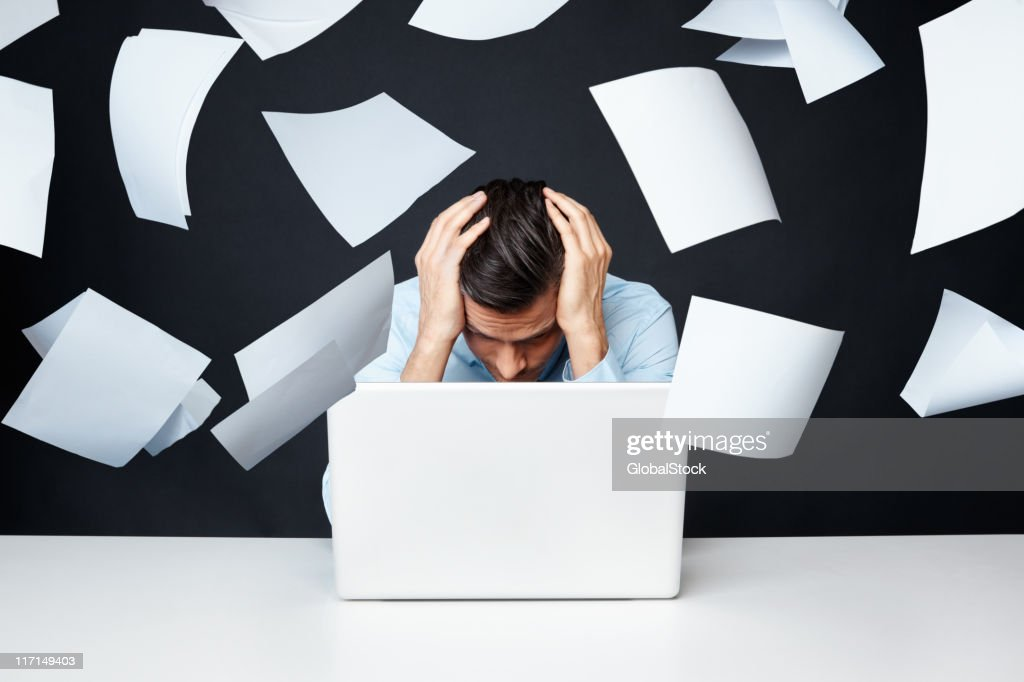 Man with hand on head looking at laptop with papers flying : Stock Photo