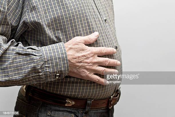 Man with hand on his stomach to depict indigestion