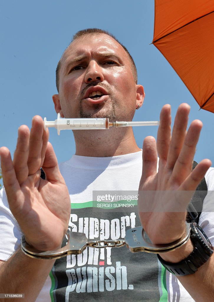 A man with handcuffs holds a syringe on June 26, 2013 during the 'Support. Don't Punish' public street event in the center of the Ukrainian capital of Kiev. People who use drugs legally or illegaly, their parents and medical workers protest against cruel and senseless state policies, which severely affect the lives of tens of thousands convicted for possessing a small amount of drug substances for personal use. Protesters called for an end to the blossoming 'drug corruption' in the law enforcement structures. The protest was organized on the occasion of the International Day against Drug Abuse and illicit Trafficking, as well as the International Day in support of Victims of Torture within the framework of the global 'Support. Don't punish' campaign to the held at the same time in 26 capitals and big cities of the world.