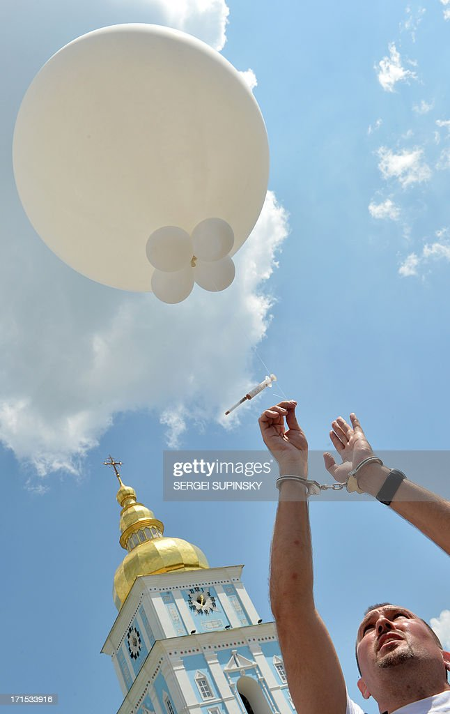 A man with handcuffs releases a balloon carrying a syringe on June 26, 2013 during the 'Support. Don't Punish' public street event in the center of the Ukrainian capital of Kiev. People who use drugs legally or illegaly, their parents and medical workers protest against cruel and senseless state policies, which severely affect the lives of tens of thousands convicted for possessing a small amount of drug substances for personal use. Protesters called for an end to the blossoming 'drug corruption' in the law enforcement structures. The protest was organized on the occasion of the International Day against Drug Abuse and illicit Trafficking, as well as the International Day in support of Victims of Torture within the framework of the global 'Support. Don't punish' campaign to the held at the same time in 26 capitals and big cities of the world. AFP PHOTO/ SERGEI SUPINSKY
