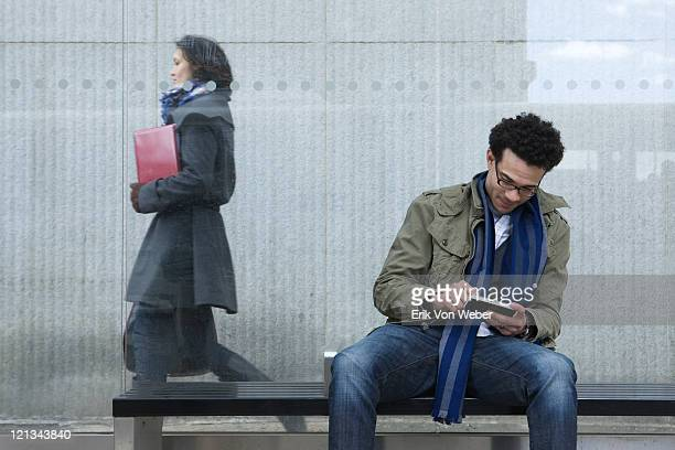 man with handheld device at bus stop